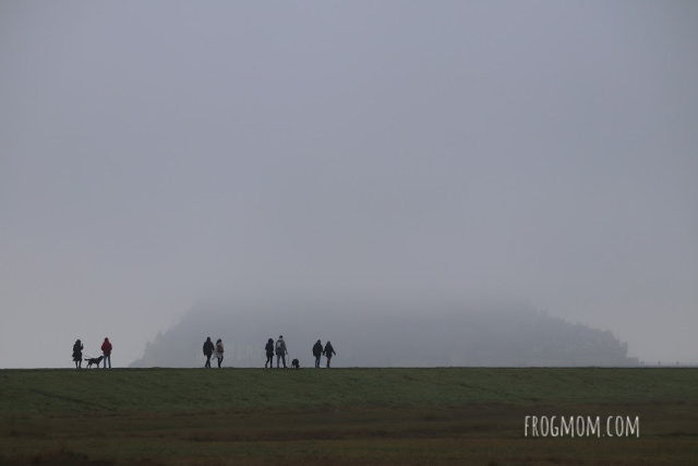 Mont St Michel in the fog with pedestrians on the walkway