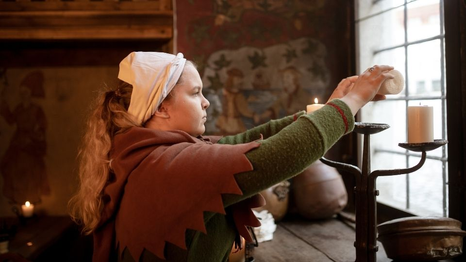 Woman lighting candles at Olde Hansa, Tallinn