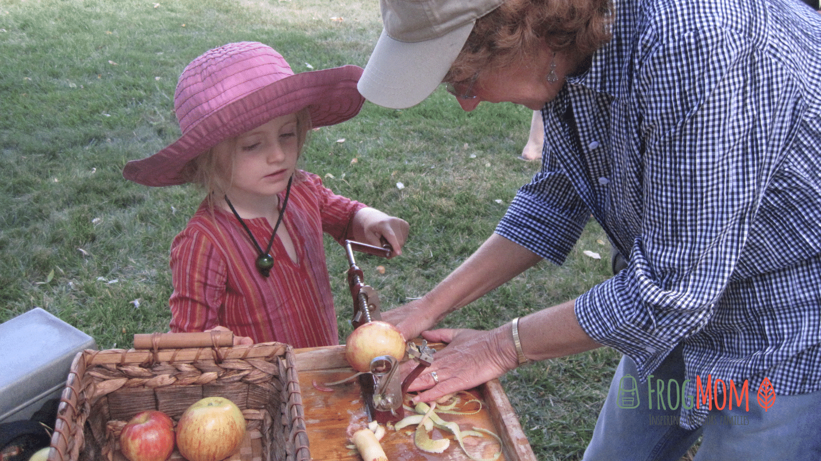 Child peeling an apple with an old-fashioned apple peeling machine at Ravenswood Historic Site's harvest festival, Applefest